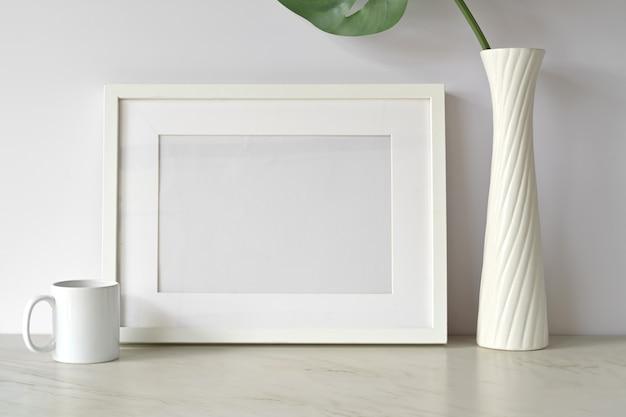 Bianco mock up frame e gadget sul tavolo bianco. Foto Premium
