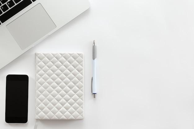 Bianco scrivania con una parte di laptop, telefono cellulare, penna Foto Gratuite