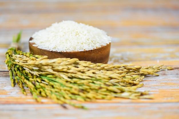 Bianco tailandese del riso sulla ciotola e di legno - grano crudo del riso del gelsomino con l'orecchio dei prodotti agricoli della risaia per alimento in asiatico Foto Premium