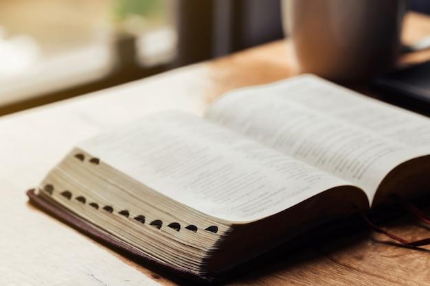 Bibbia aperta con una tazza di caffè per devozione mattutina sul tavolo di legno Foto Premium