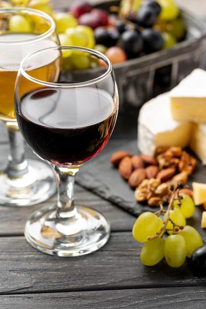 Bicchiere ad alto angolo con vino e snack per degustazione Foto Gratuite