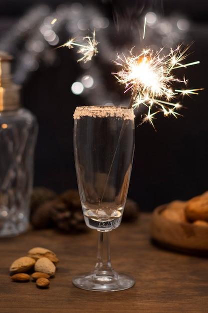 Bicchiere con champagne e fuochi d'artificio Foto Gratuite