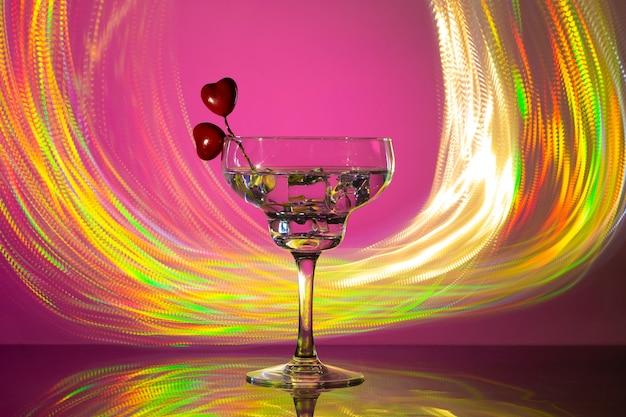 Bicchiere con un cocktail e due cuori. san valentino e concetto di matrimonio. Foto Premium