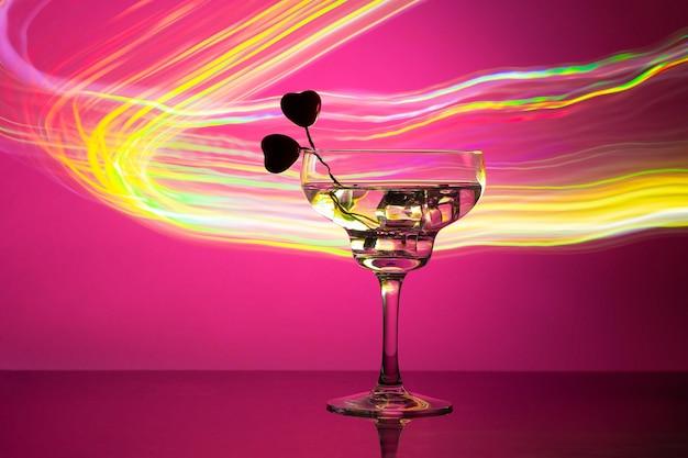 Bicchiere con un cocktail e due cuori. Foto Premium