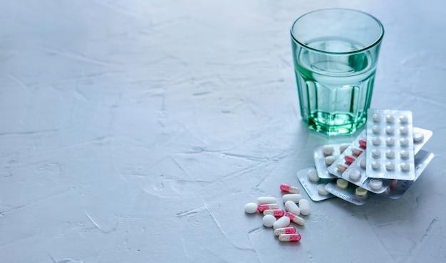 Bicchiere d'acqua con pillole e compresse sulla superficie grigia. Foto Premium