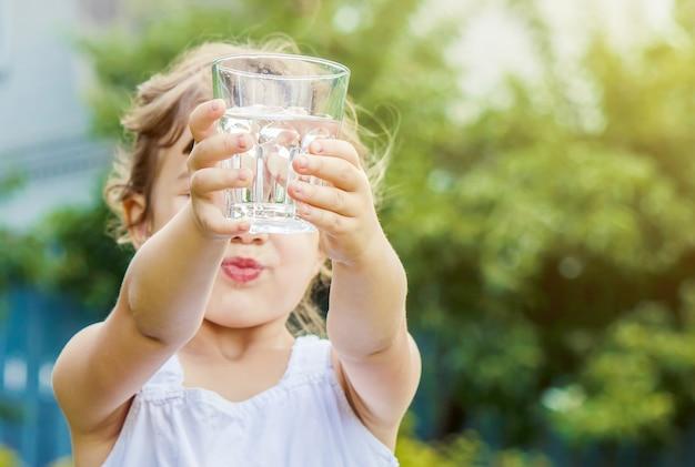 Bicchiere d'acqua da bambino. messa a fuoco selettiva. Foto Premium