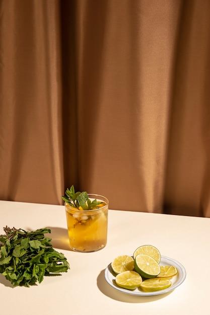 Bicchiere da cocktail con foglie di menta e fette di lime sul tavolo bianco contro la tenda marrone Foto Gratuite