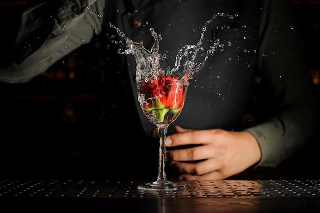 Bicchiere da cocktail con spruzzi di bevanda alcolica e bocciolo di rosa in esso Foto Premium