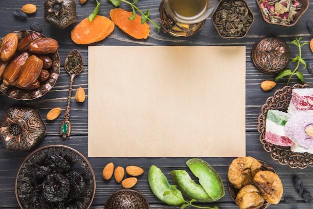 Bicchiere da tè con diversi tipi di frutta secca, noci e carta Foto Gratuite