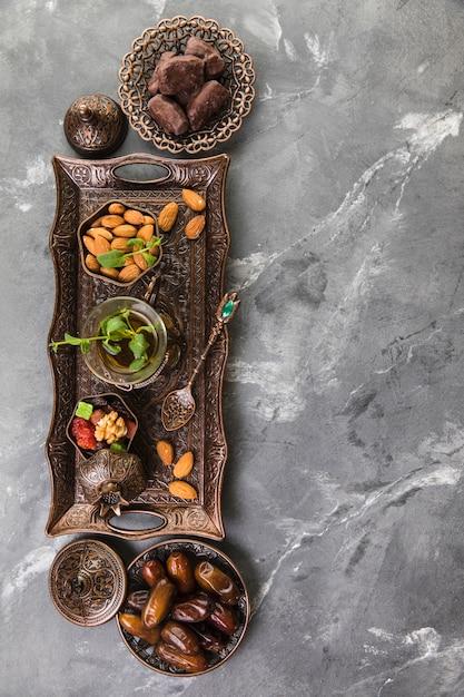 Bicchiere da tè con frutta data e mandorle sul vassoio Foto Gratuite