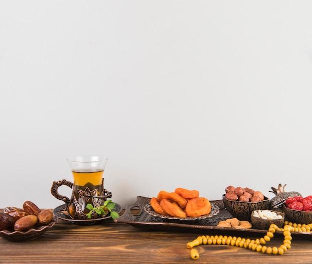 Bicchiere da tè con frutta secca e perline sul tavolo Foto Gratuite