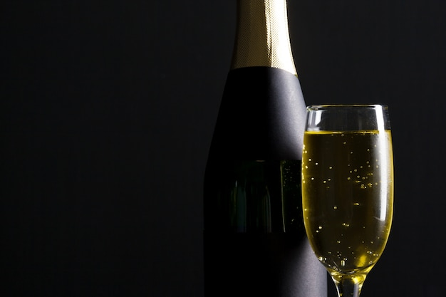 Bicchiere da vino e bottiglia di champagne sul nero Foto Premium