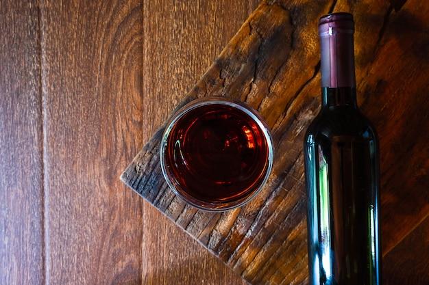 Bicchiere da vino e bottiglia di vino sul tavolo di legno Foto Premium