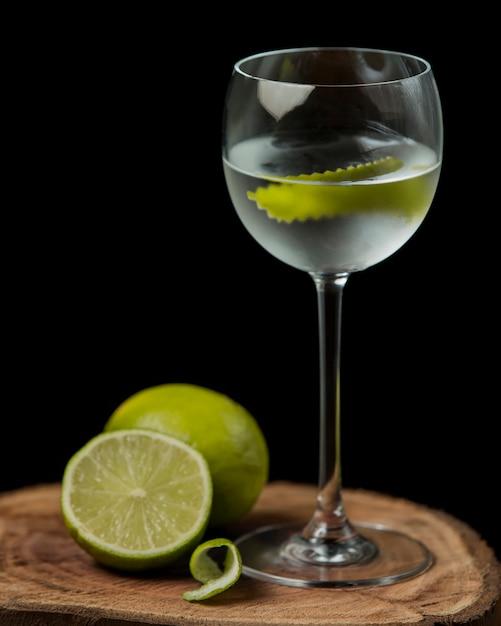 Bicchiere di acqua di calce con scorza di lime su tavola di legno Foto Gratuite