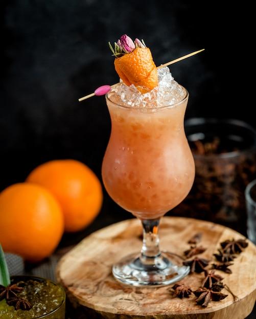 Bicchiere di arancia ghiacciata cocktail guarnito con scorza d'arancia a forma di fragola Foto Gratuite