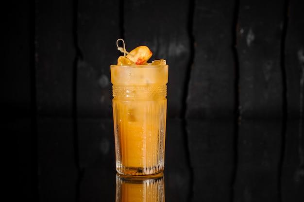 Bicchiere di bevanda alcolica fresca con ghiaccio decorato con pezzi di pesca Foto Premium