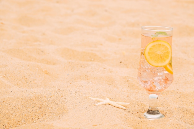 Bicchiere di bevanda refrigerante con fette di agrumi e stelle marine Foto Gratuite