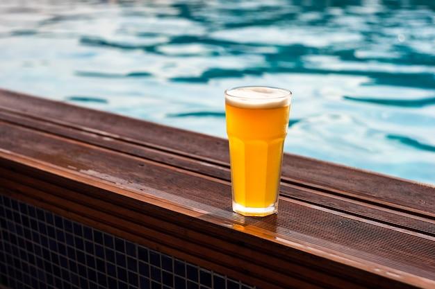 Bicchiere di birra a bordo piscina Foto Premium