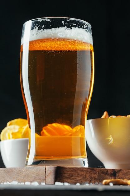 Bicchiere di birra chiara con ciotole snack Foto Premium