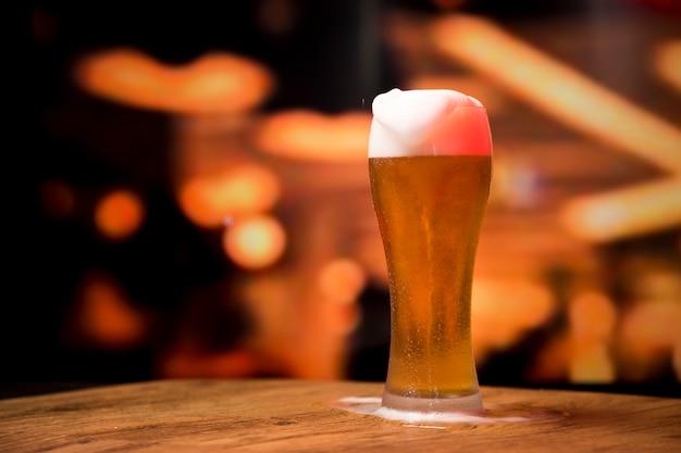 Bicchiere di birra davanti a sfondo sfocato Foto Gratuite