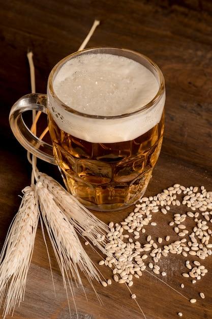 Bicchiere di birra leggera con orzo a spillo sul tavolo di legno Foto Gratuite
