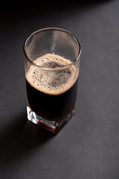 Bicchiere di birra scura su uno sfondo scuro con texture in legno Foto Premium