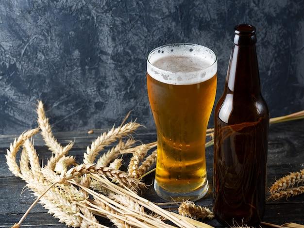 Bicchiere di birra su una pietra scura con bottiglia di birra e copia spazio di grano Foto Premium