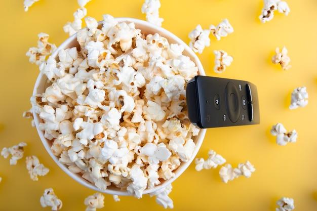 Bicchiere di carta di popcorn, telecomando tv, vista dall'alto. guardare il cinema Foto Premium