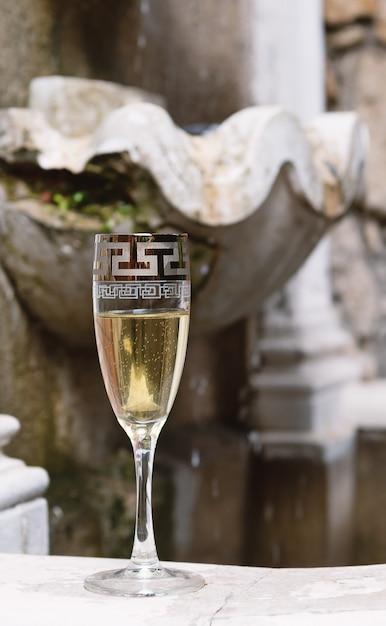 Bicchiere di champagne e fontana in background. Foto Premium