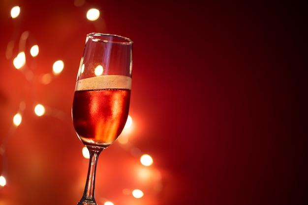 Bicchiere di champagne sul tavolo contro luci sfocate Foto Premium