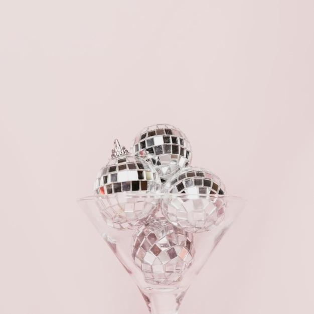 Bicchiere di champagne trasparente con palline da discoteca Foto Gratuite