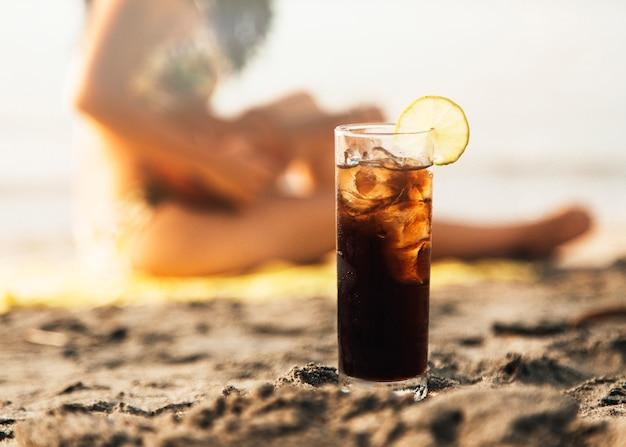 Bicchiere di coca cola con ghiaccio sulla spiaggia Foto Gratuite