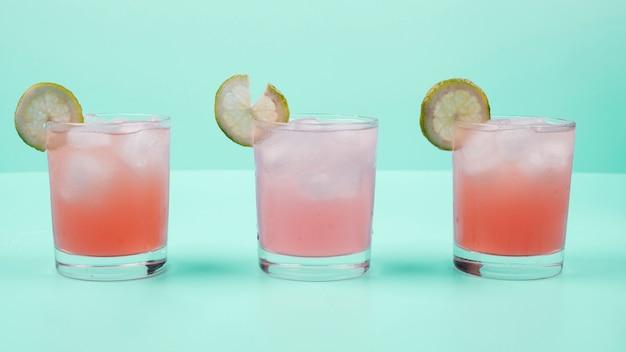 Bicchiere di cocktail bere con fetta di limone e cubetti di ghiaccio su sfondo di menta Foto Gratuite