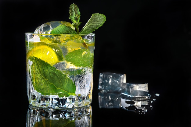 Bicchiere di cocktail con rum, lime, cubetti di ghiaccio e foglie di menta su sfondo nero a specchio. Foto Premium