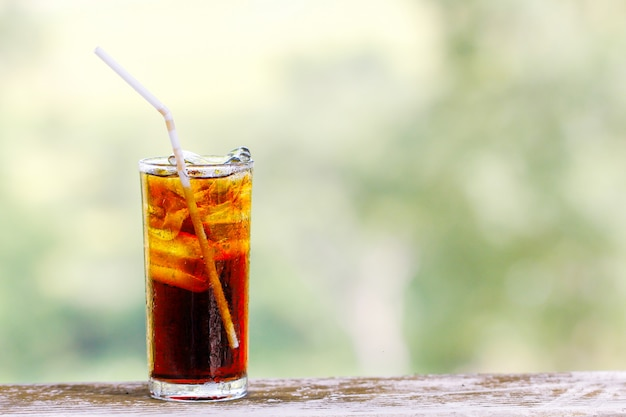Bicchiere di cola con cubetti di ghiaccio sul tavolo di legno. Foto Premium