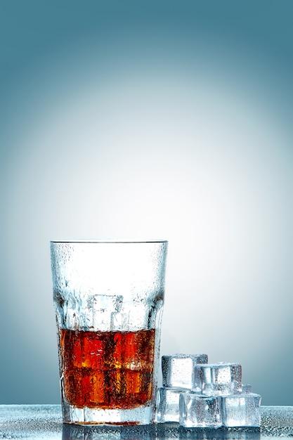 Bicchiere di cola con cubetti di ghiaccio Foto Gratuite
