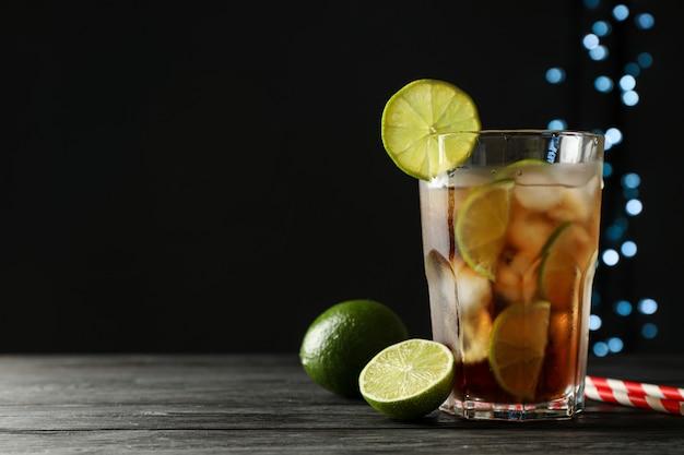 Bicchiere di cola fredda con agrumi e ghiaccio sul tavolo di legno su sfondo scuro Foto Premium