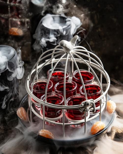 Bicchiere di colpi con bevanda rossa servita nella torta nella padella affumicata Foto Gratuite