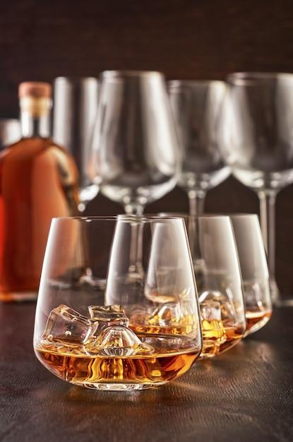 Bicchiere di cristallo con whisky su un tavolo di legno Foto Premium