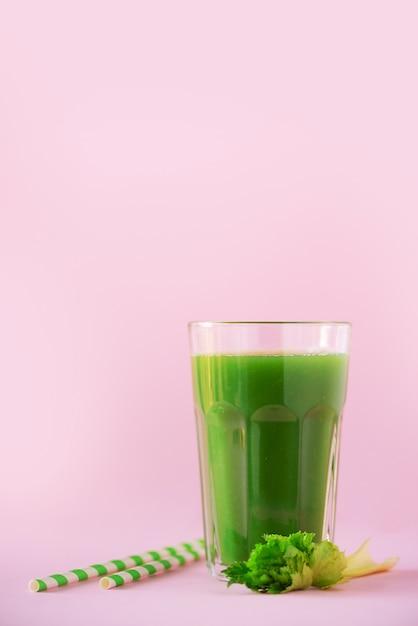 Bicchiere di frullato di sedano verde su sfondo rosa Foto Premium