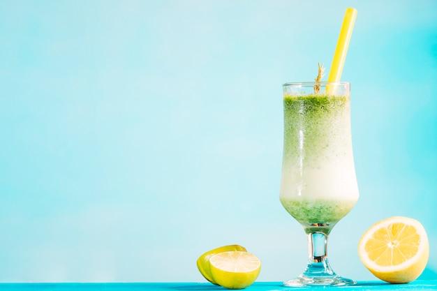 Bicchiere di frullato verde cremoso e agrumi a fette Foto Gratuite