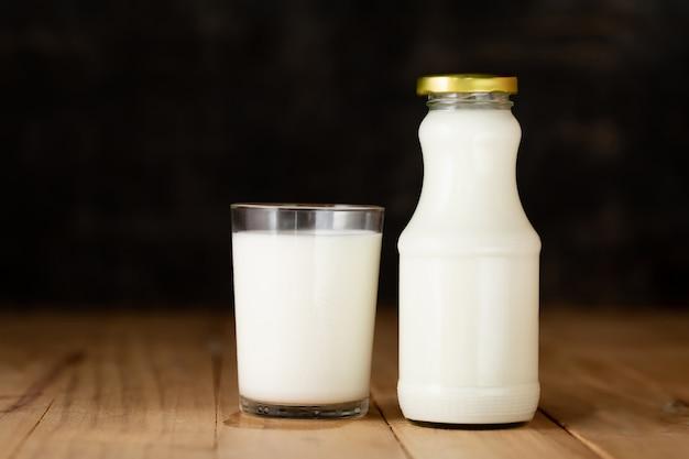 Bicchiere di latte e una bottiglia di latte fresco Foto Gratuite