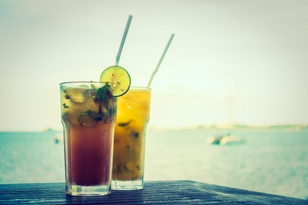 Bicchiere di mojito di ghiaccio con l'oceano tropicale del mare Foto Gratuite