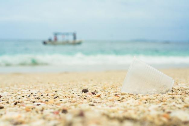 Bicchiere di plastica nel riciclaggio della spiaggia Foto Premium