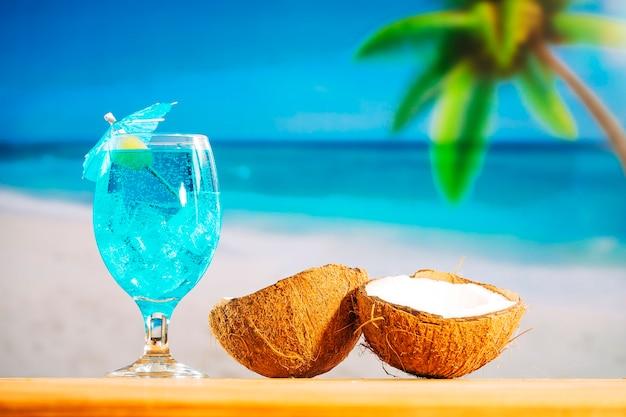 Bicchiere di raffreddamento bevanda blu e noci di cocco incrinate Foto Gratuite