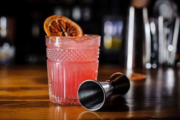 Bicchiere di rosa cocktail alcolici decorato con una fetta di arancia Foto Premium