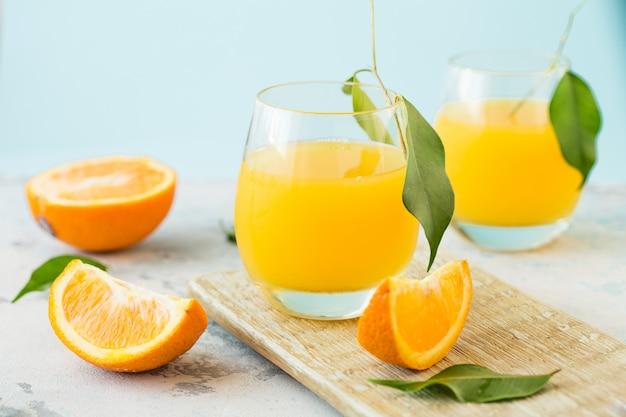 Bicchiere di succo d'arancia fresco con gruppo di arance Foto Premium