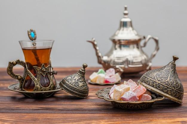 Bicchiere di tè con delizia turca e teiera Foto Gratuite