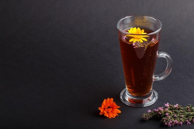 Bicchiere di tisana con calendula e issopo su sfondo nero. vista laterale, copia spazio. Foto Premium