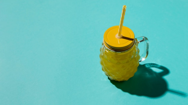 Bicchiere di vetro con coperchio giallo e paglia Foto Gratuite